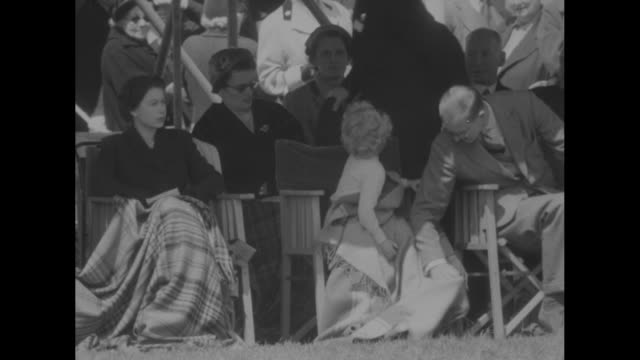 royal family attends royal horse show superimposed over horse jumping fence / queen elizabeth ii young princess anne prince philip draped in blankets... - horse blanket stock videos & royalty-free footage