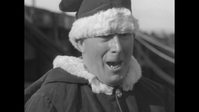 Title 'Santa Claus Comes out of the Arctic Youngsters on Captain Bob's little Morrissey get a Christmas treat' / 'Santa Claus' stands on deck with a...