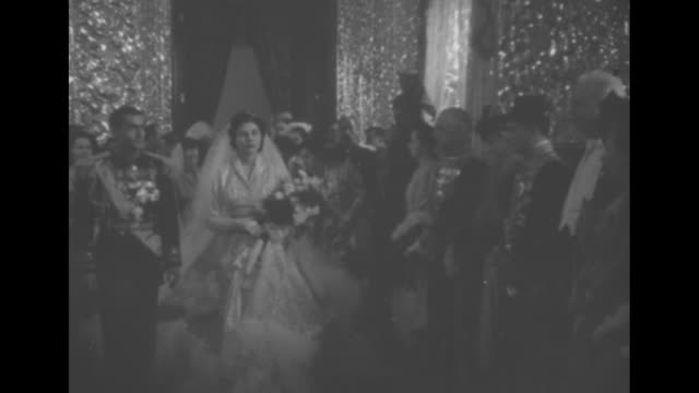 Title Shah of Iran Wedding of the year superimposed over Shah Mohammad Reza Pahlavi standing next to his bride Princess Soraya both posing for photo...