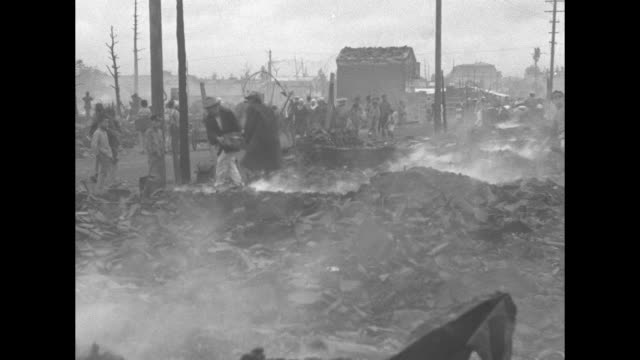 stockvideo's en b-roll-footage met shibata japan superimposed on smoking rubble and japanese people walking on street / people with aftermath of fire / men picking through smoke barren... - soeplepel