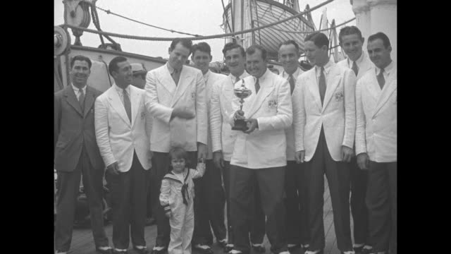 ship news superimposed over ship's funnel / us ryder cup golf team stands on ship deck in white suit jackets / cu ryder cup trophy / cu team captain... - heavyweight stock videos and b-roll footage