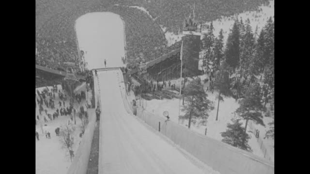'Spectacular Ski Jumping Ends Winter Olympics' superimposed over people standing at top of ski jump / three aerial shots of ski jump / view from top...