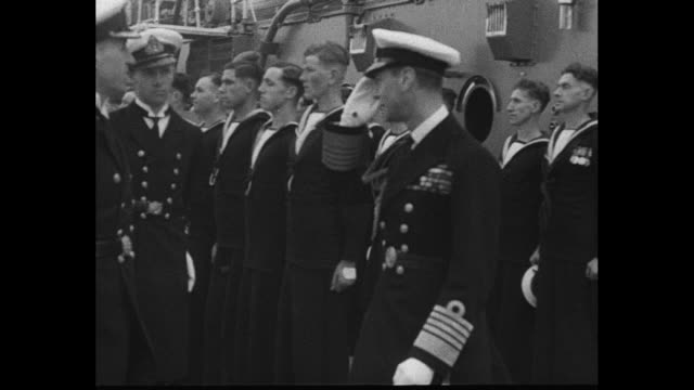 spithead england superimposed over view of british fleet in bay / king george vi and queen elizabeth greet and shake hands with naval officers... - 1937 stock-videos und b-roll-filmmaterial