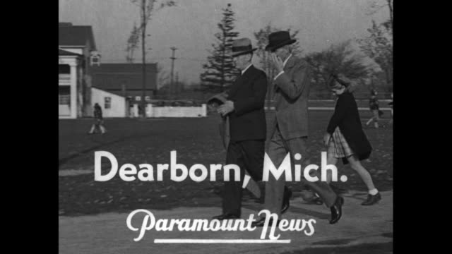 title superimposed dearborn mich on ford walking with eagle tavern in the distance and girls following him / note exact day not known - dearborn michigan stock videos & royalty-free footage