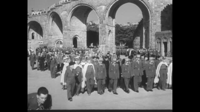 Title superimposed 'French vets in pilgrimage to Lourdes' / soldiers some in capes with Roman arch at rear / vast crowd / litters with injured or...