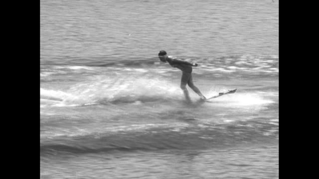 title superimposed on a water skier down under wizards on water skis / vs man seen from a camera boat falling another lets go of the rope and goes... - beauty stock videos & royalty-free footage