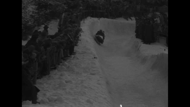 title superimposed on bobsledders bobsled teams defy turns on bavaria course / man pushes sled jumps in behind teammate / vs sleds speeding on... - bobsleighing stock videos & royalty-free footage