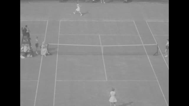 "title superimposed on connolly, ""maureen connolly is youngest champ"" / maureen connolly serves during tennis match / man in crowd with backwards... - baseball cap stock videos & royalty-free footage"