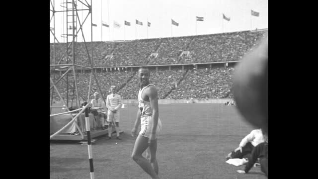 title superimposed on german athlete luz long òbroad jumpó / vs american jesse owens walks infield before jump / pan with owens running with jump /... - 1936 stock-videos und b-roll-filmmaterial