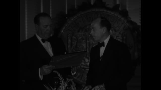 Title superimposed on insignia Photoplay magazine's film awards / Photoplay editor Fred Sammis gives award to director David Butler for Calamity Jane...