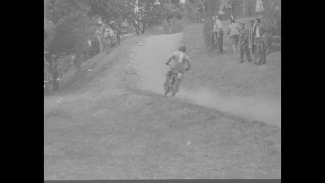 """title superimposed on motorcycle race """"motorcycle grand prix of italy!"""" / vs riders speed along in clouds of dust / vs motorcycles flying over hill,... - name unknown film title点の映像素材/bロール"""