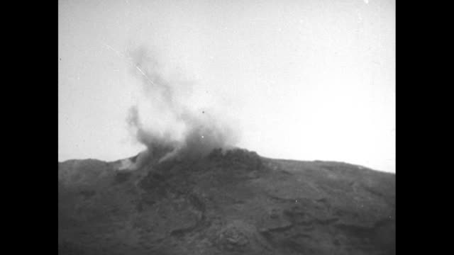 title superimposed on mount suribachi 1945 the flag goes up on iwo jima / vs explosion at the top of mount suribachi men hunkered down on a beach... - schlacht um iwojima stock-videos und b-roll-filmmaterial