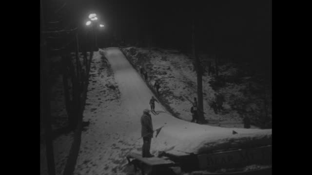 title superimposed on nighttime ski ramp night owl ski meet / vs skiers under powerful lights fly off ramp and come to stop on snowy track far below - snowy owl stock videos and b-roll footage