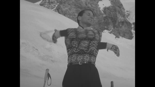 Title superimposed on snowcovered mountains 'Switzerland Fashions on skis' / VS six people on skis lifting left legs placing skis in awkward...