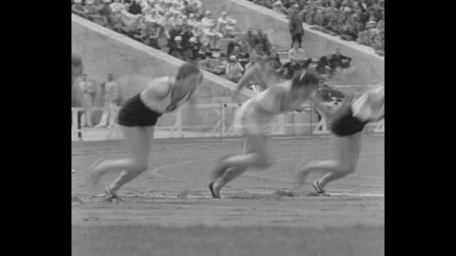 title superimposed on women at racing starting block 100 meter / race begins / high angle view of racers far below and packed grandstands / us's... - podio video stock e b–roll