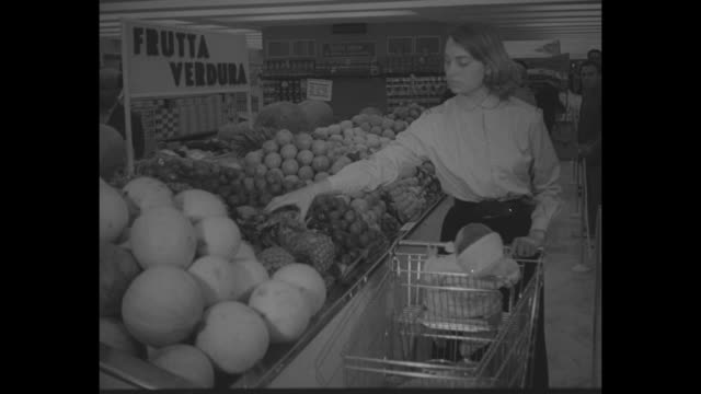 title supermarket us style opens in rome / crowd inside market / woman with cart takes a pineapple and cantaloupe / turkey removed from case / man... - 1950 stock videos & royalty-free footage
