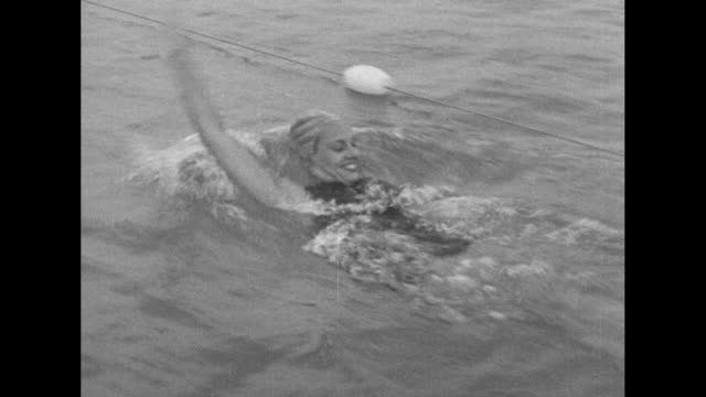 """swimming"" over swimmers diving into water and crossing pool / eleanor holm swims backstroke / holm, out of water, smiles / title: ""diving"" over shot... - backstroke stock videos & royalty-free footage"