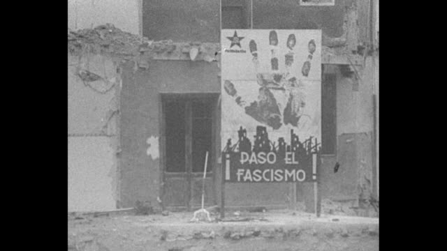 "vídeos y material grabado en eventos de stock de ""tetuan"" superimposed over bombed building / whole corner section of seven-story building destroyed by bomb / tilt up through bombed corner / sign in... - fascismo"