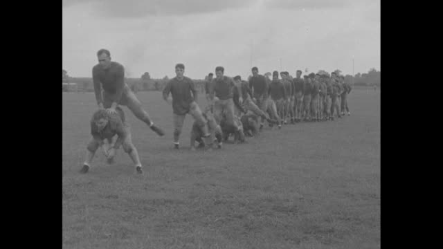 title the camera reporter superimposed over cameraman behind turning movie camera / lsu football players leapfrog over each other / players take... - hoppa bock bildbanksvideor och videomaterial från bakom kulisserna
