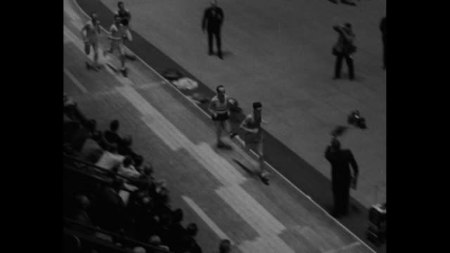 the millrose games superimposed over aerials of track meet / millrose games at madison square garden / 5 men compete in the wanamaker mile race /... - men's track stock videos and b-roll footage