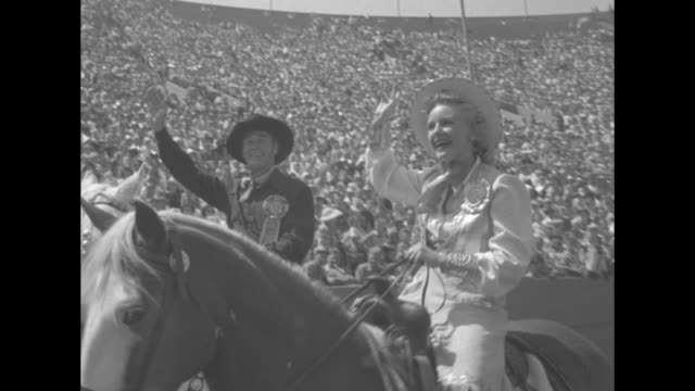 The Sheriff Stages a Rodeo superimposed over aerial of rodeo in portion of L A Coliseum / L A County Sheriff Eugene Biscailuz on horse holding up...
