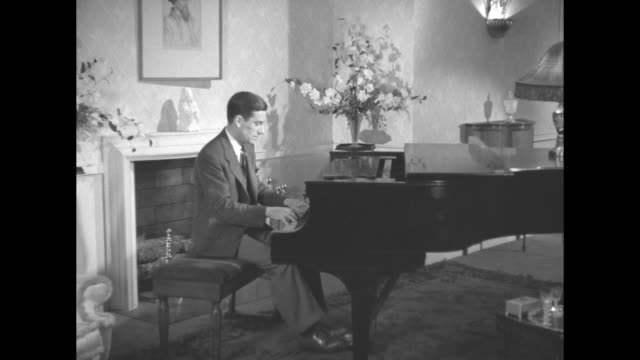 title top tunes remember stardust hoagy carmichael / carmichael seated at grand piano in parlor plays / note exact year not known documentation... - hoagy carmichael stock videos & royalty-free footage