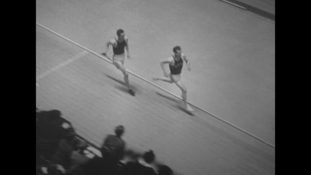 vidéos et rushes de track and field superimposed over indoor track meet / runners approach as they round curve of track / tiltdown shot glenn cunningham and gene venzke... - piste de compétition