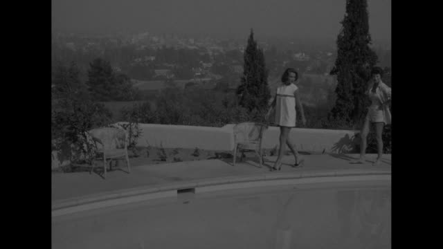 Under the southern sun superimposed on swimming pool / woman with pleated skirted bathing suit leans against diving board as another joins her /...
