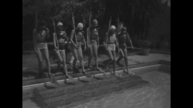 Underwater Rifle Girls superimposed over women swimming underwater / front view of women lined up on edge of swimming pool wearing underwater masks...