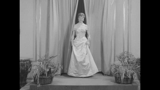 'Vienna Preview Of Fall Fashions' superimposed over door opening to salon in House of Adlemuller and model coming through curtain onto stage and...