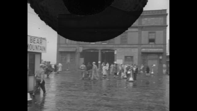 title warner club boat ride june 15 1948 / men walk on rainy pavement past ticket booths marked sightseeing around manhattan bear mountain toward... - fahrkartenschalter stock-videos und b-roll-filmmaterial