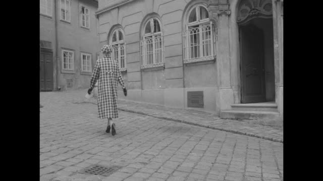 title weather wise raincoats go traveling superimposed on vienna street / woman wearing checkered raincoat walks on cobblestones / ext building /... - oresund region stock videos and b-roll footage