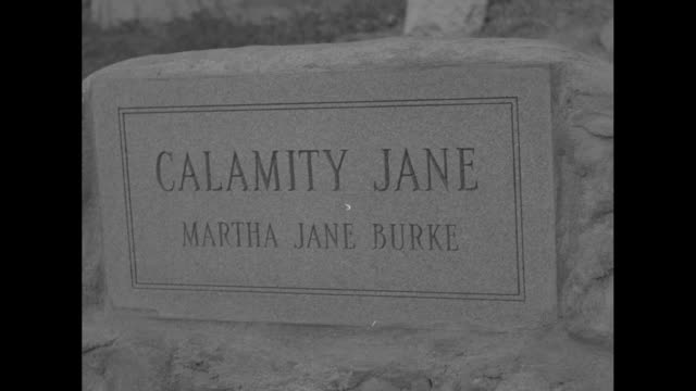 western style premier for calamity jane superimposed over parade / actressimpersonator looks down on calamity jane memorial headstone / cu headstone... - 彫刻画点の映像素材/bロール