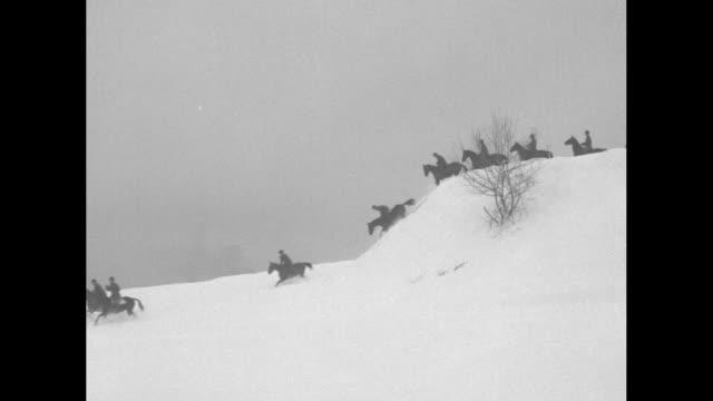 vídeos y material grabado en eventos de stock de title winter tests cavalry superimposed over cadets galloping on horses through snow past camera / line of cadets galloping on horses through snow... - cavalry