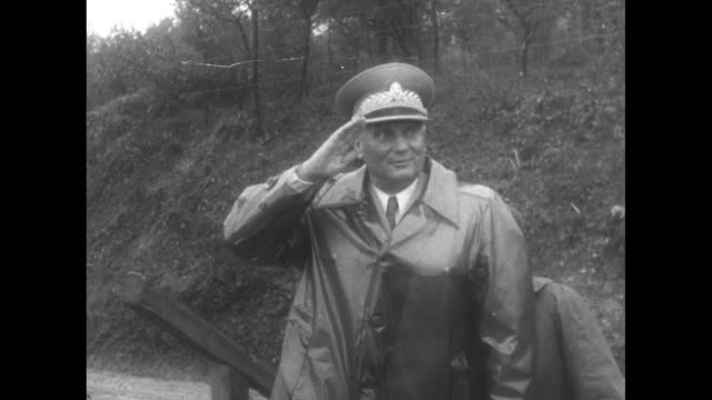 world news / title tito shows army's might on maneuvers superimposed over josip broz tito talking to soldier / tito wearing raincoat saluting and... - 旧ユーゴスラビア点の映像素材/bロール