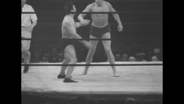 'Wrestling' superimposed over two men and referee in wrestling ring during match / VS wrestlers Danno O'Mahony and Jim Londos at match / man jumps...
