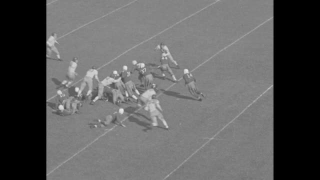 stockvideo's en b-roll-footage met yale 12 navy 7 superimposed over navy midshipman standing in formation on field in municipal stadium pan across midshipman standing in formation /... - maryland staat