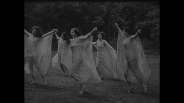 'Yes Sir It's Spring superimposed over US Capitol seen through branches with cherry blossoms on them / four women in thin gowns dance in circle on...