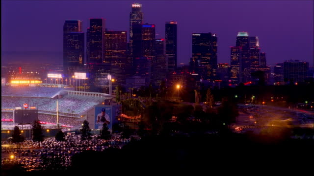 Tiume lapse high angle wide shot panning from downtown skyline to Dodger Stadium / night / Los Angeles, California