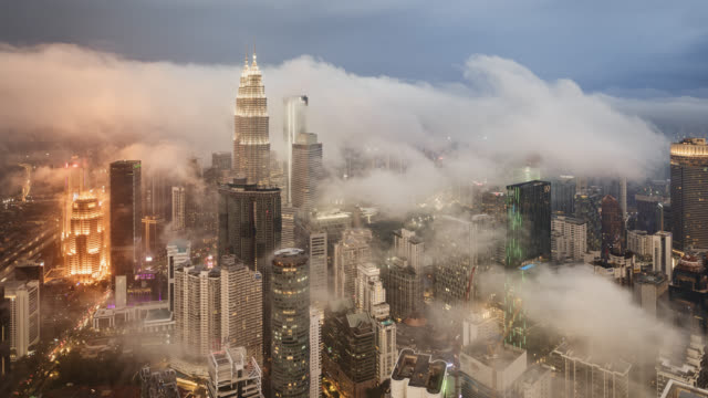 vidéos et rushes de tl/ms day to night timelapse lapse of kuala lumpur skyline and financial district and petronas towers, during tropical storm, with mist - brouillard