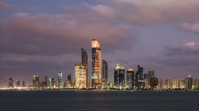 tl/zi day to night zoom in time lapse of the abu dhabi skyline, and financial district, with the arabian sea in foreground - oil industry stock videos & royalty-free footage