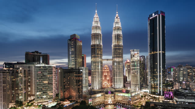tl/zi day to night zoom in time lapse/hyper lapse of the petronas towers and kuala lumpur skyline and financial district - petronas twin towers stock-videos und b-roll-filmmaterial