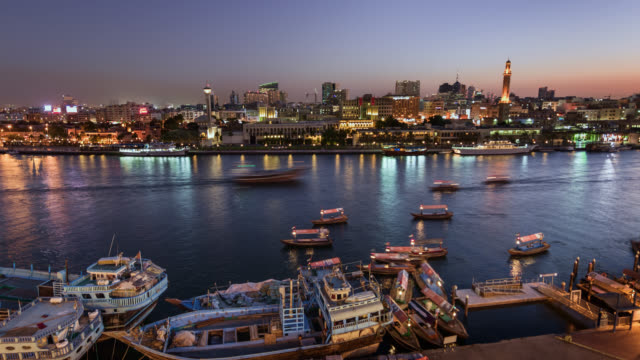 tl/zo day to night zoom out time lapse of dubai creek and spice market, at sunset with passing cargo boats and traffic. - middle east stock videos & royalty-free footage