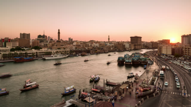 tl/zo day to night zoom out time lapse of dubai creek and spice market, at sunset with passing cargo boats and traffic. - martin luther: his life and time stock videos & royalty-free footage