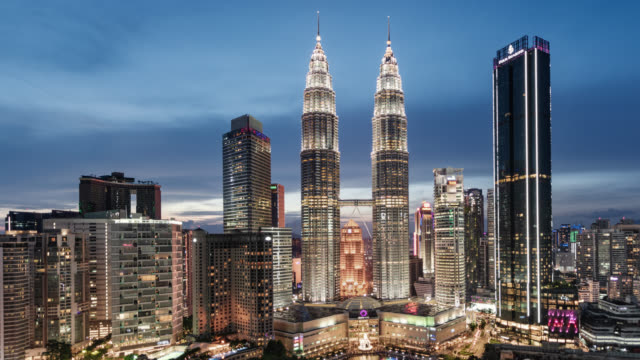 tl/zo day to night zoom out time lapse/hyper lapse of the petronas towers and kuala lumpur skyline and financial district - petronas twin towers stock-videos und b-roll-filmmaterial