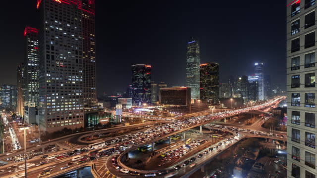 tl/pd/pan down time lapse of busy road intersection in beijing's financial district, with traffic and commuters at rush hour - beijing stock videos & royalty-free footage