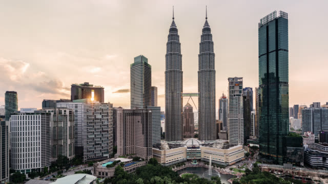 tl/zi zoom in time lapse/ hyper lapse of the petronas towers and kuala lumpur skyline at sunset - petronas twin towers stock-videos und b-roll-filmmaterial