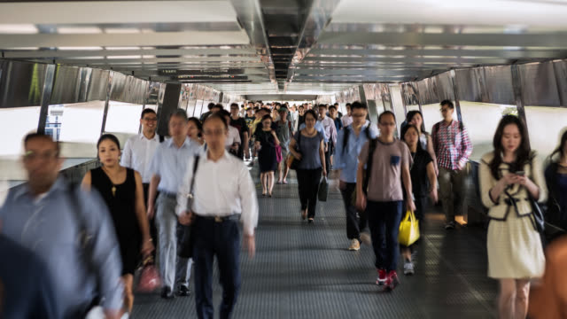 tl/zo zoom out time lapse of hong kong's financial district, with commuters during morning rush hour, using elevated walkway - wealth stock videos & royalty-free footage
