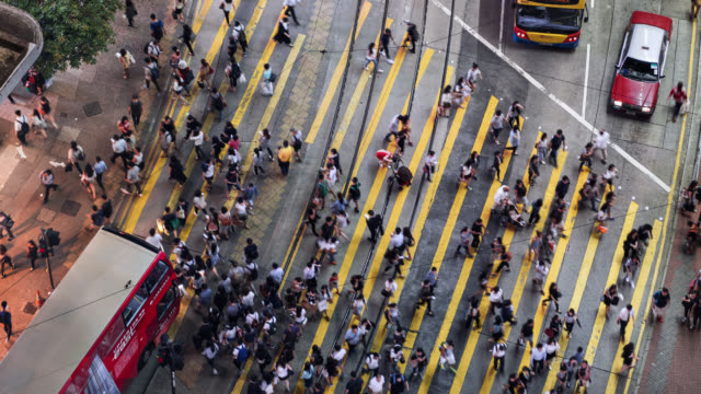tl/zo zoom out time lapse of people and commuters crossing pedestrian crossing in central hong kong, aerial view - pedestrian video stock e b–roll