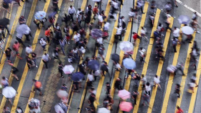 tl/zo zoom out time lapse of people and commuters crossing pedestrian crossing in central hong kong, aerial view - price stock videos & royalty-free footage